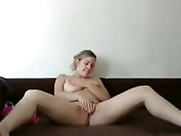 Busty sexy nudes gets naked on the sofa and fingers her pussy