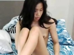 Skinny young Asian lies in bed and exposes her tiny tits an
