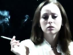 Cute brunette is having a smoke while talking to the camera